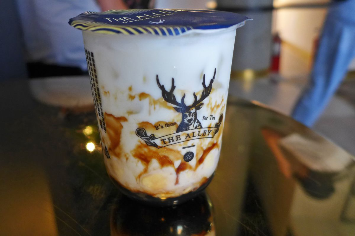 A plastic cup with a stag head on the side and brown and white liquid in layers...