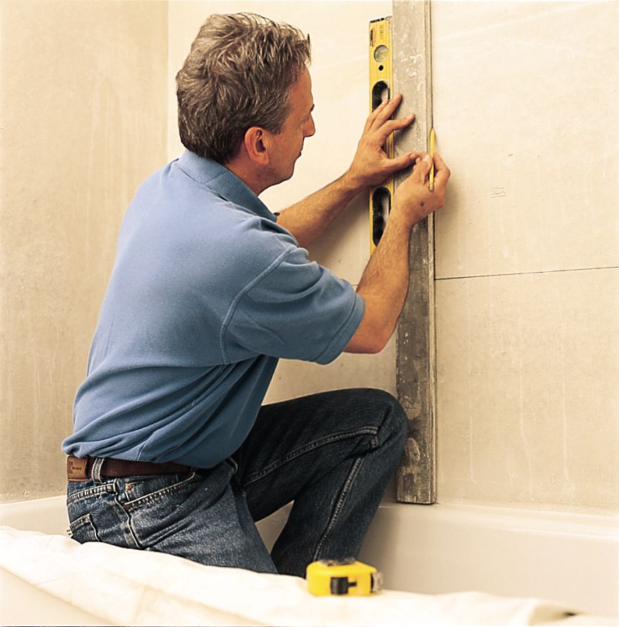 Man Marks Layout To Prepare For Tile Surround