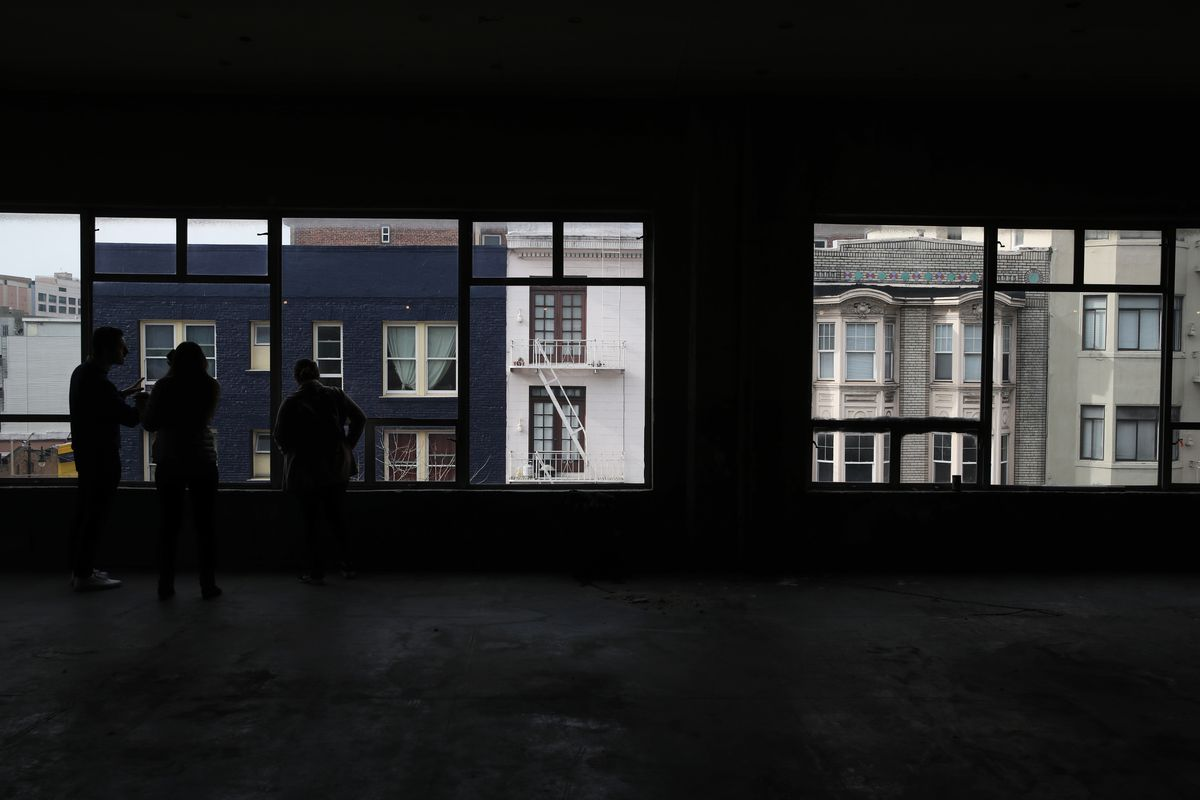Four silhouettes of people standing in the middle of an almost entirely empty room, looking out a row of windows that make up one entire wall.