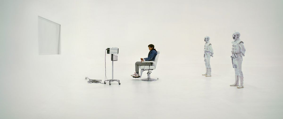A small, distant figure in blue sits in an all-white room, in front of a white screen and some white equipment, with two figures in all-white armor standing behind the chair.