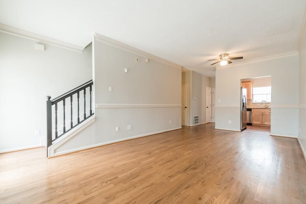 Empty living space with staircase on the left and opening into kitchen in the back.