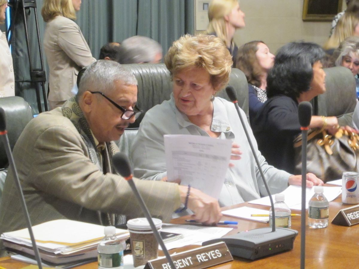 Regents Luis Reyes and Beverly Ouderkirk go over some paperwork at July's Board of Regents meeting.