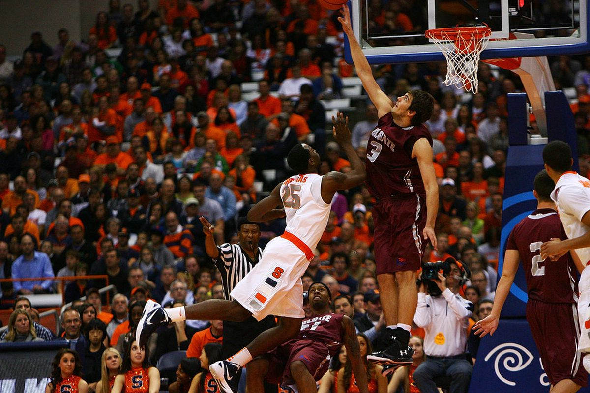 SYRACUSE, NY - NOVEMBER 19:  Rakeem Christmas #25 of the Syracuse Orange dives as he shoots the ball against John Brandenburg #3 of the Colgate Raiders during the game at the Carrier Dome on November 19, 2011 in Syracuse, New York.