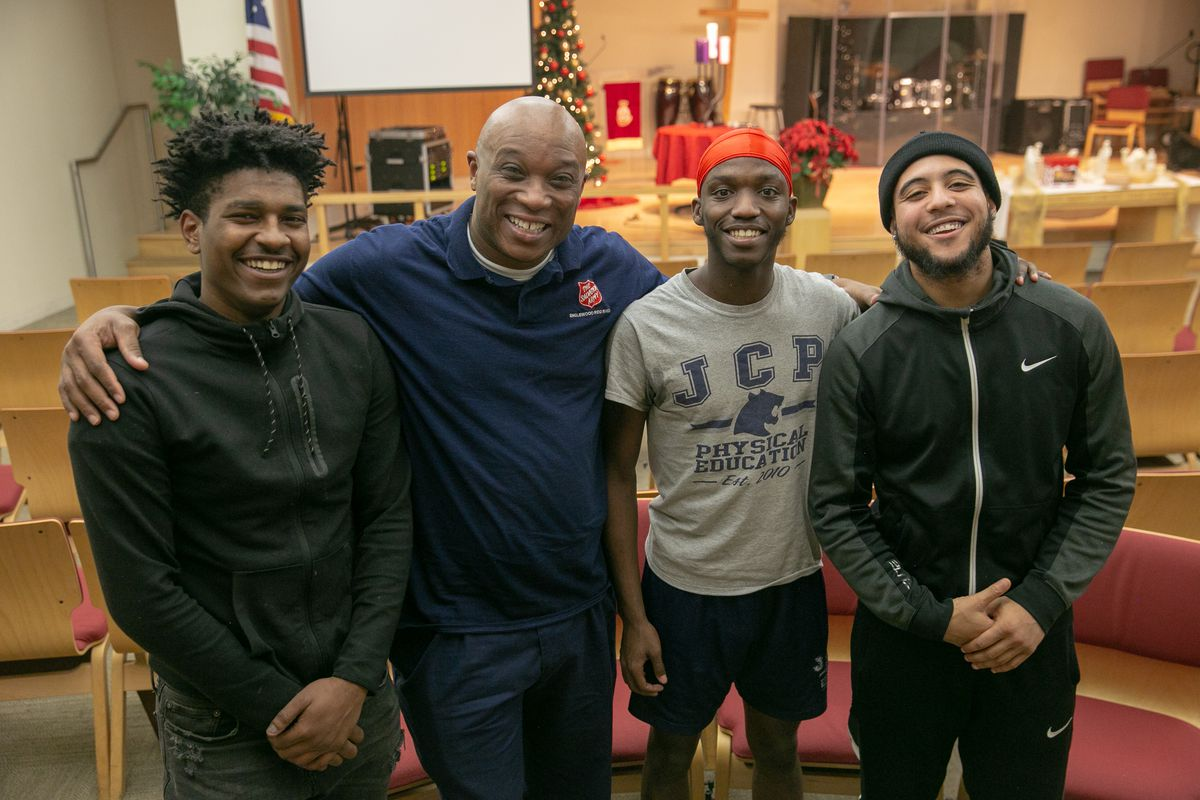 (From left to right) At the Salvation Army Red Shield Center in Englewood, mentee Carl Velez, 21, Corps Ministries Director Theo Coleman, and mentees Isaac House, 18, and Jaridian Lee, 19, gather for the Celebrate Launch and Landing mentoring program held