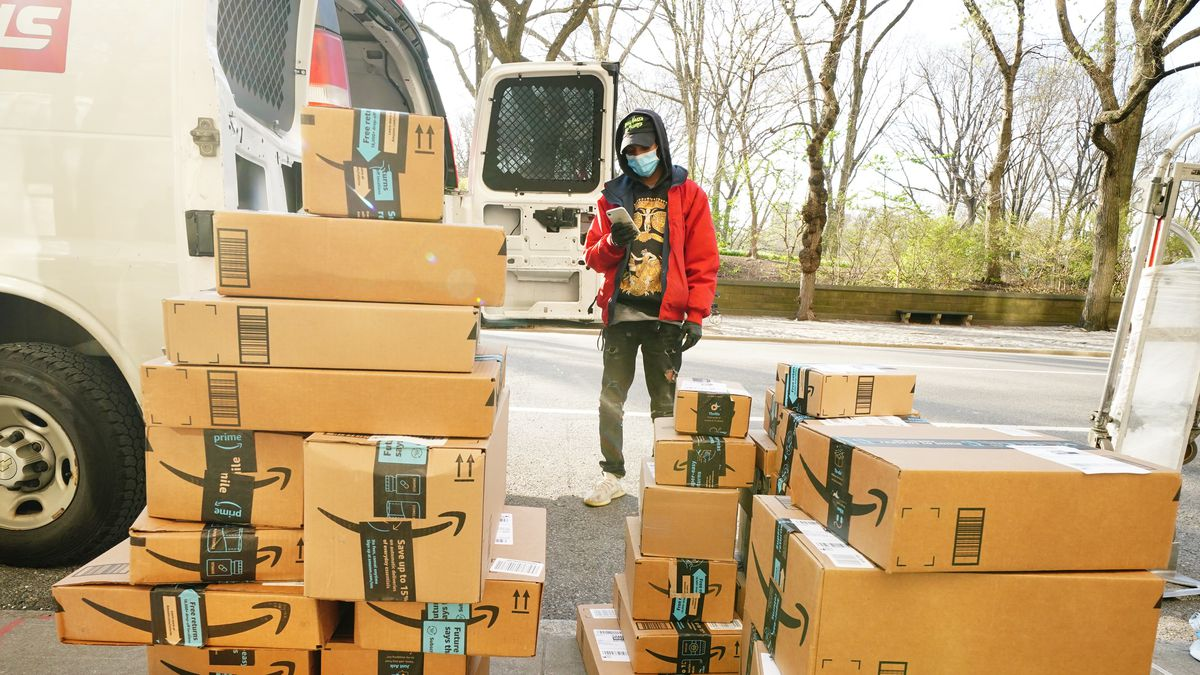A delivery person stands next to a pile of Amazon packages on the sidewalk.