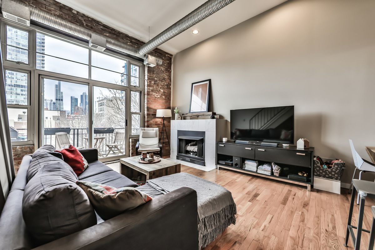 A loft with hardwood floors, a large balcony, and a exposed brick. There is a couch in front of the fireplace and tv.