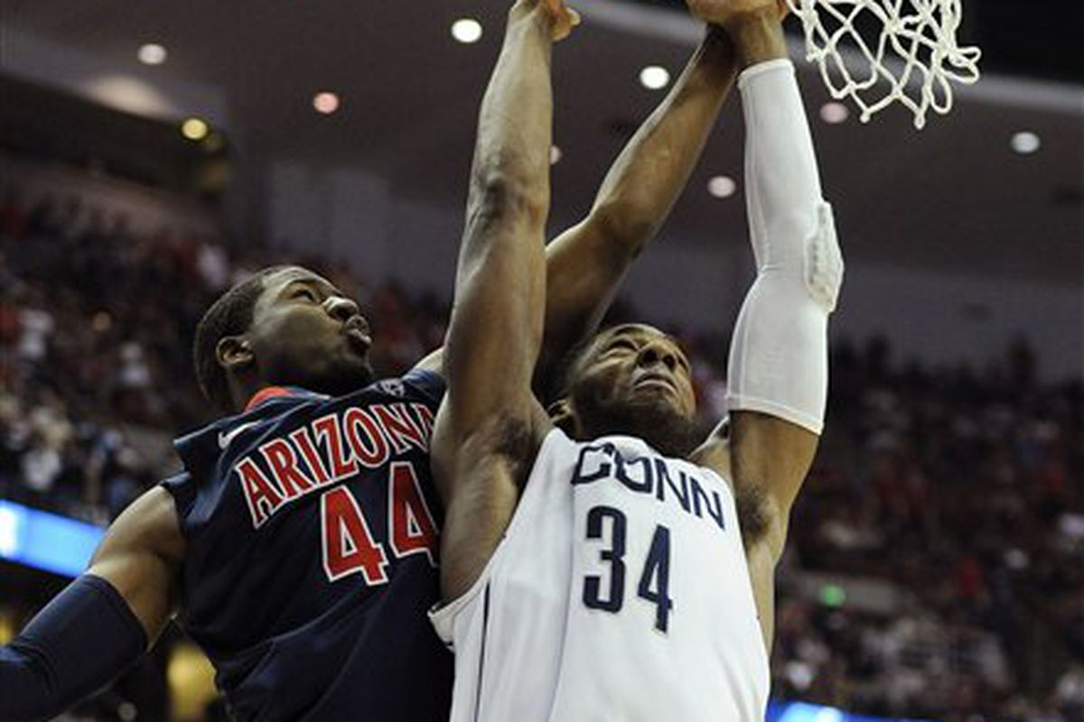 Connecticut's Alex Oriakhi gets past Arizona's Soloman Hill for a dunk in the Huskies' 65-63 win over the Wildcats to earn a trip to the NCAA Tournament Final 4.  (Photo by Mark Terrill-AP)