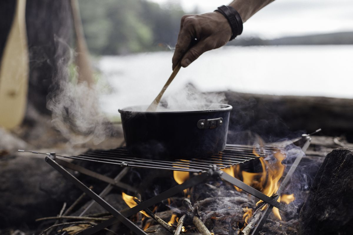 A stainless steel grill with a pot that has steam rising from it. There is a fire burning under the grill. There is a person using a wooden spoon to stir food inside of the pot.