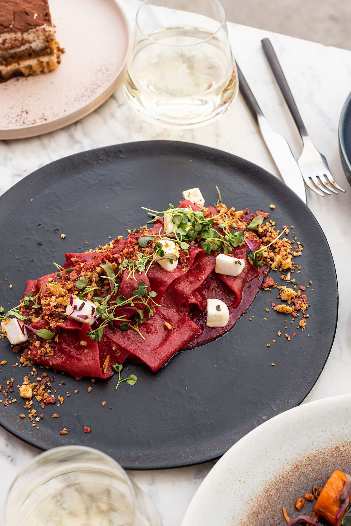 A maroon pasta sits on a dark slate plate from above.
