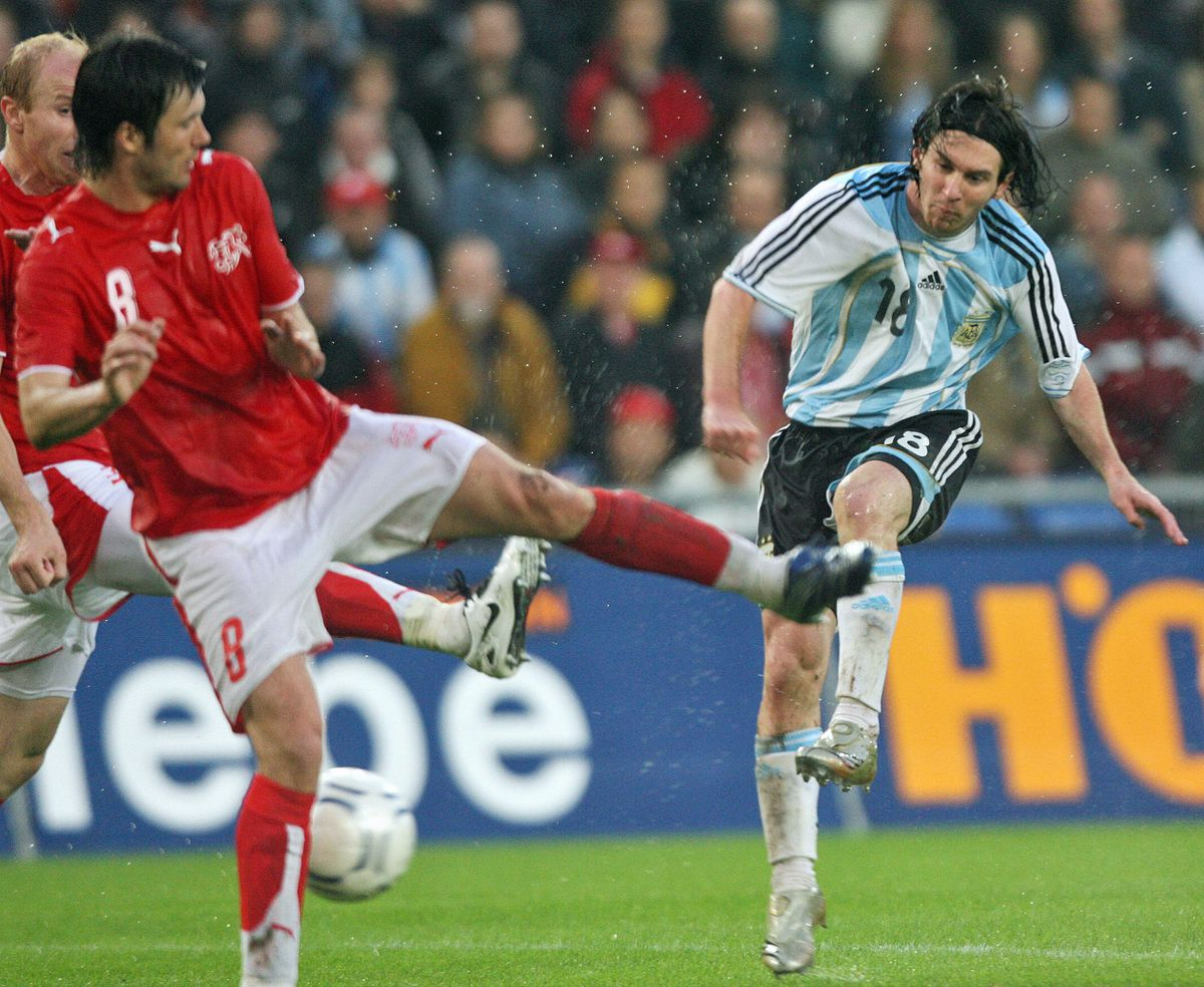 Argentina's Lionel Messi (R) fights for...