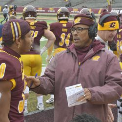 A CMU assistant coach talks to Thaddeus Cornick during a pause in play.
