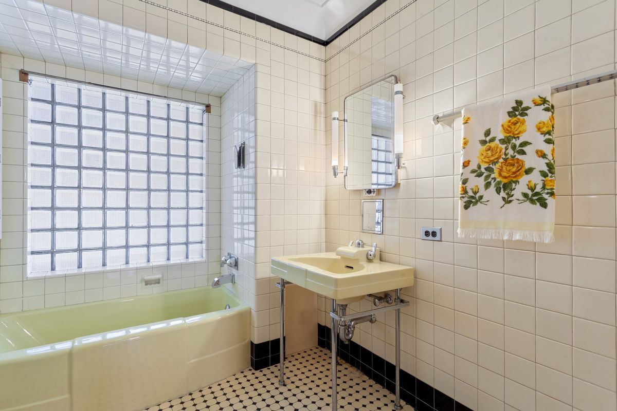 One of the bathrooms with a glass block window and pedestal sink. There is white tile with black trim.