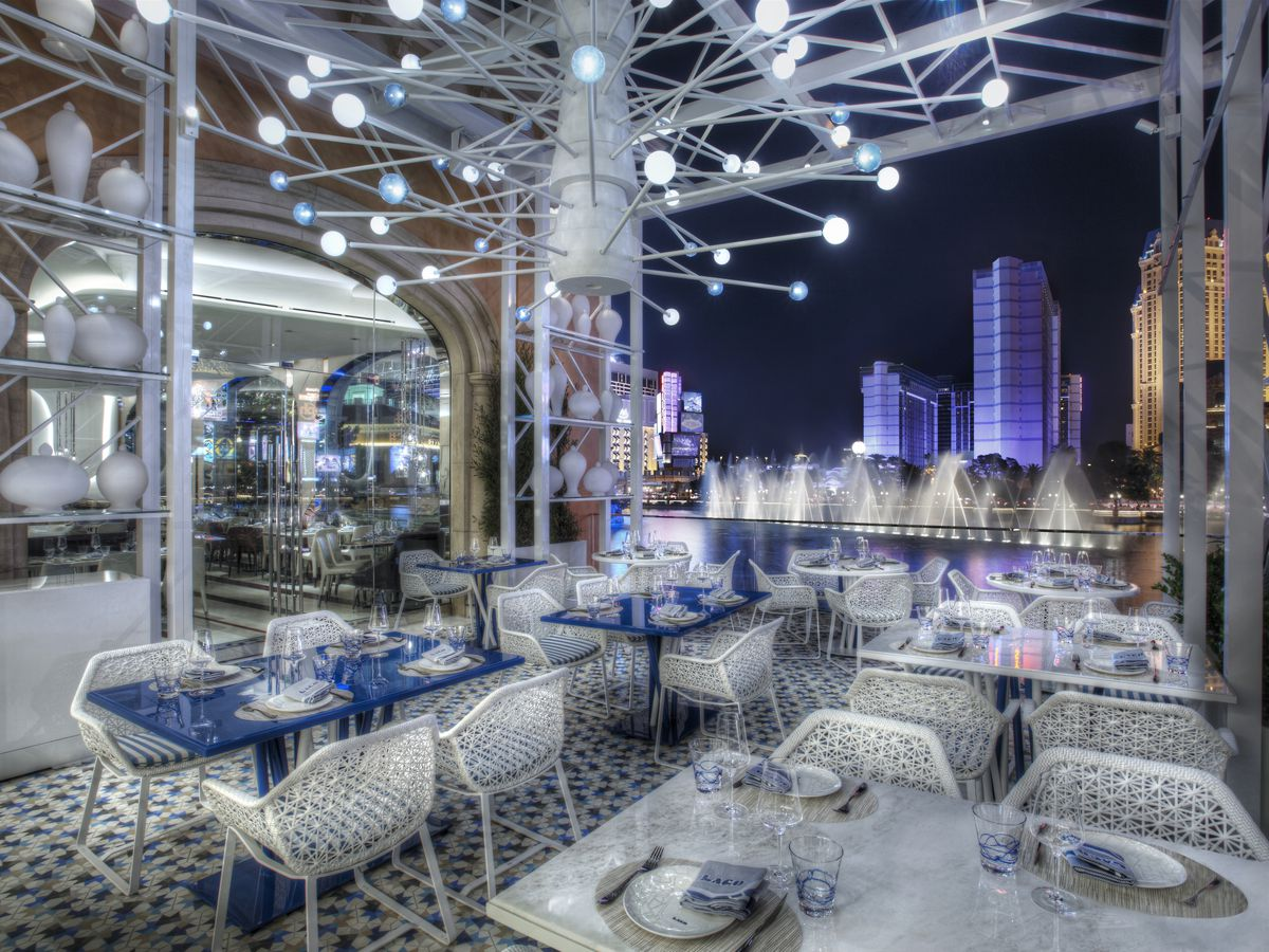 A dramatic patio at night with white chairs and a fountain behind it
