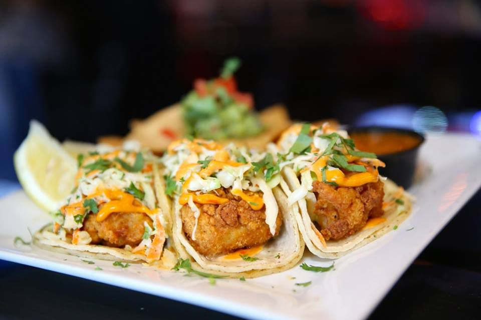Three fish tacos aligned on a plate.