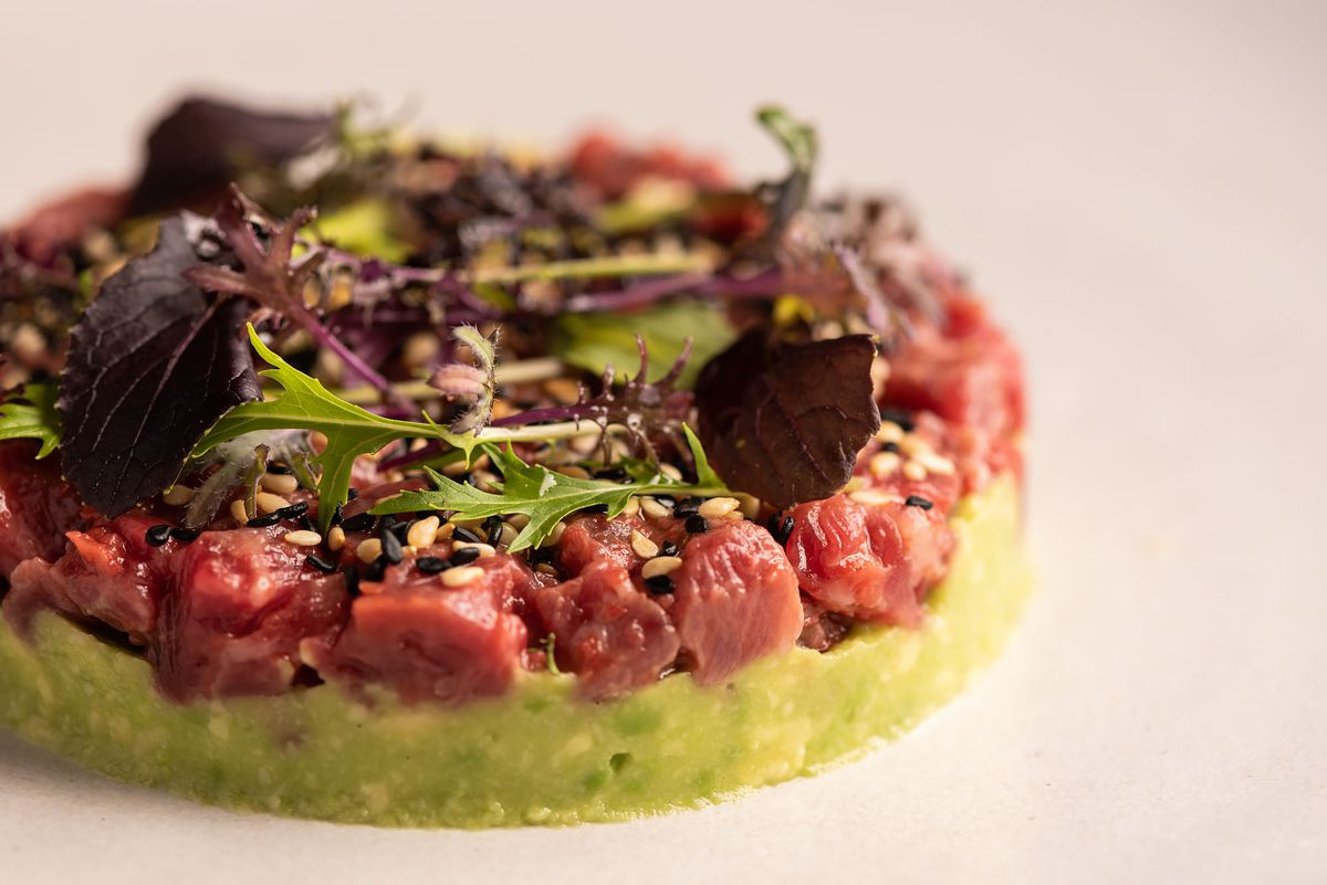 A close up shot of steak tartare with greens.
