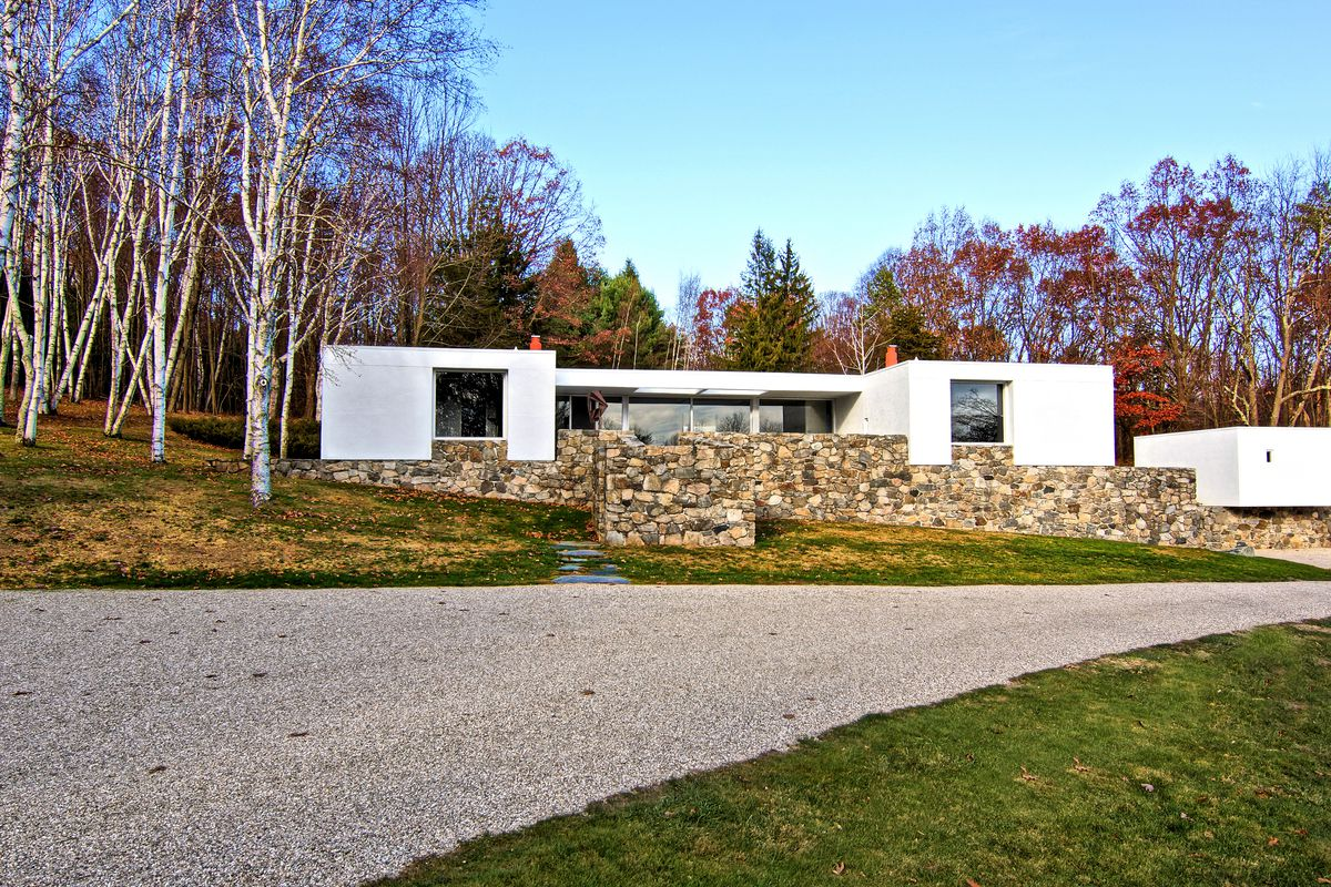 White cubic volume set on top of a platform of stone set against New England woods.