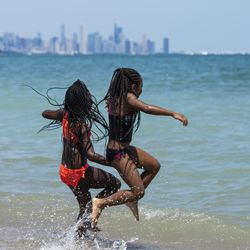 (From left) Cousins Andrea Martin, 9, and 9-year-old Samarri Mills, both from the South Shore neighborhood, jump in Lake Michigan at Rainbow Beach on the South Side, Wednesday afternoon, July 24, 2019.