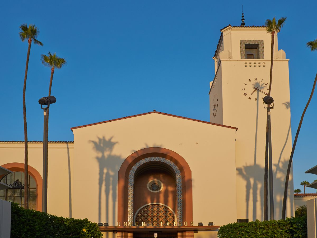A large tan building. There are tall palm trees in front of the building.