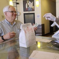 Michael McPhee picks up a to-go order from The Robin's Nest in Salt Lake City on Tuesday, March 17, 2020. A Salt Lake County health order prohibits dine-in options for all restaurants, taverns, bars, clubs and entertainment venues in an effort to slow the spread of COVID-19.