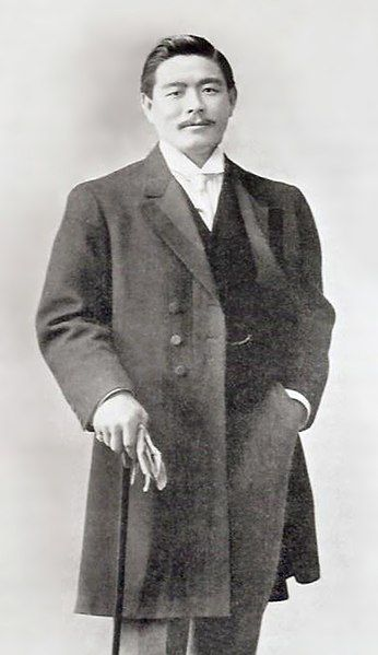 Mitsuyo Maeda standing, wearing a fine suit and overcoat, holding a cane and gloves.