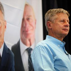 Libertarian presidential candidate Gov. Gary Johnson listens as running mate Gov. Bill Weld speaks in Salt Lake City at the University of Utah on Saturday, Aug. 6, 2016.