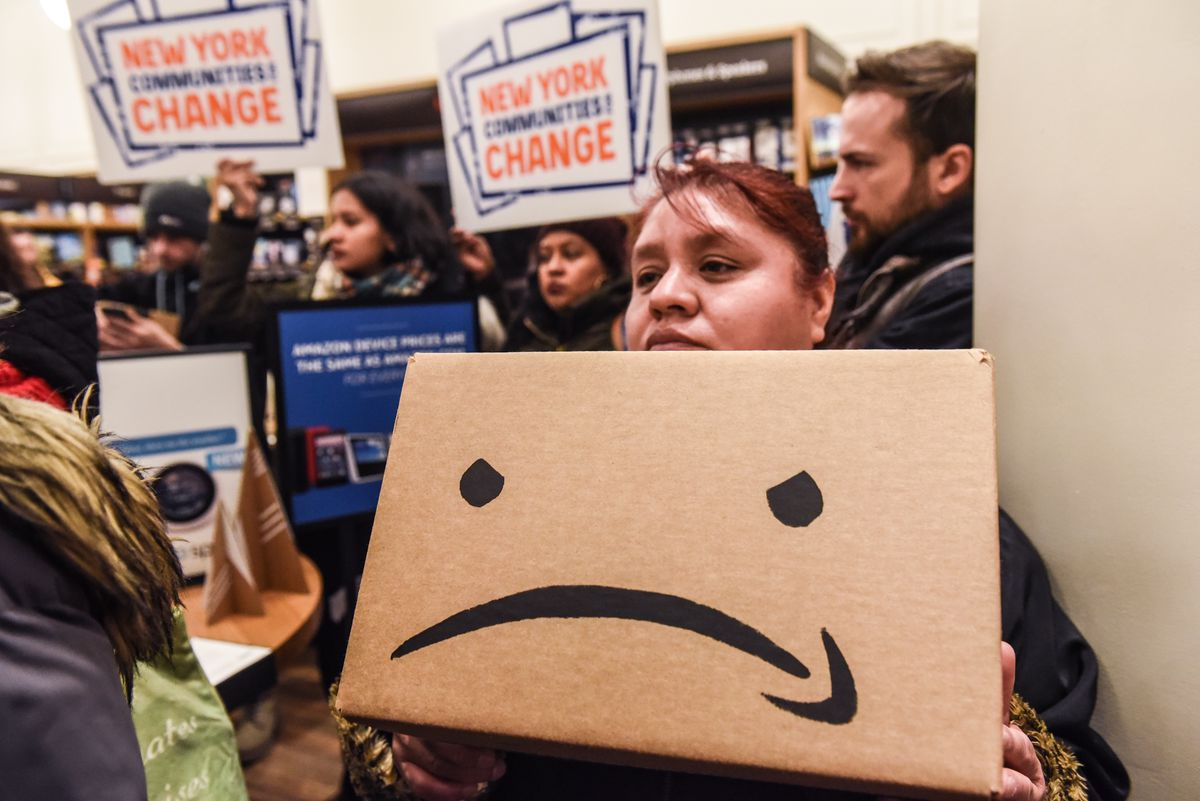 Protesters against Amazon in New York hold up signs and a box with and Amazon smile upside down.