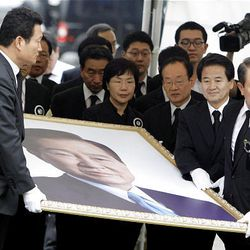 South Korean lawmakers carry a portrait of the late former South Korean President Kim Dae-Jung for a memorial service at Seoul Plaza in Seoul, South Korea, Wednesday.