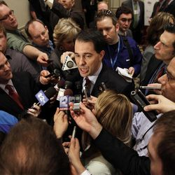 Wisconsin Gov. Scott Walker is surrounded by the news media after speaking to the Illinois Chamber of Commerce Tuesday, April 17, 2012 in Springfield, Ill. Ever since his fight to pass an anti-union bill last year, Walker has kept up a jet-setting schedule that's more akin to a candidate running for president than governor.