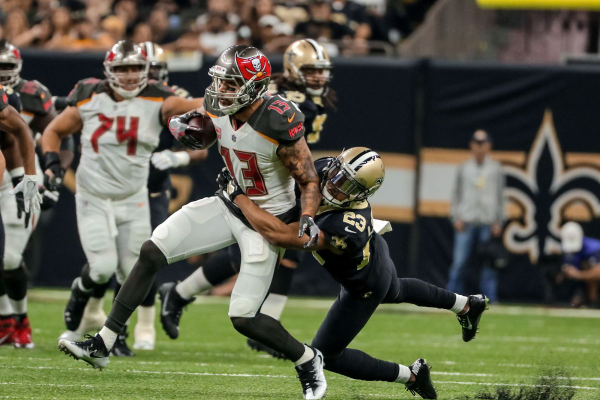 New Orleans Saints cornerback Marshon Lattimore tackles Tampa Bay Buccaneers wide receiver Mike Evans during the first half of a game at the Mercedes-Benz Superdome.