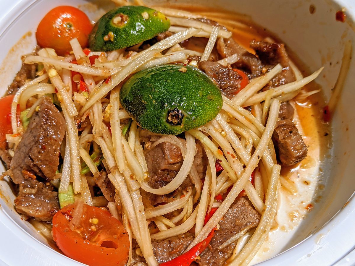 a close up of a white bowl with pieces of tomato, lime, beef, and green shoots