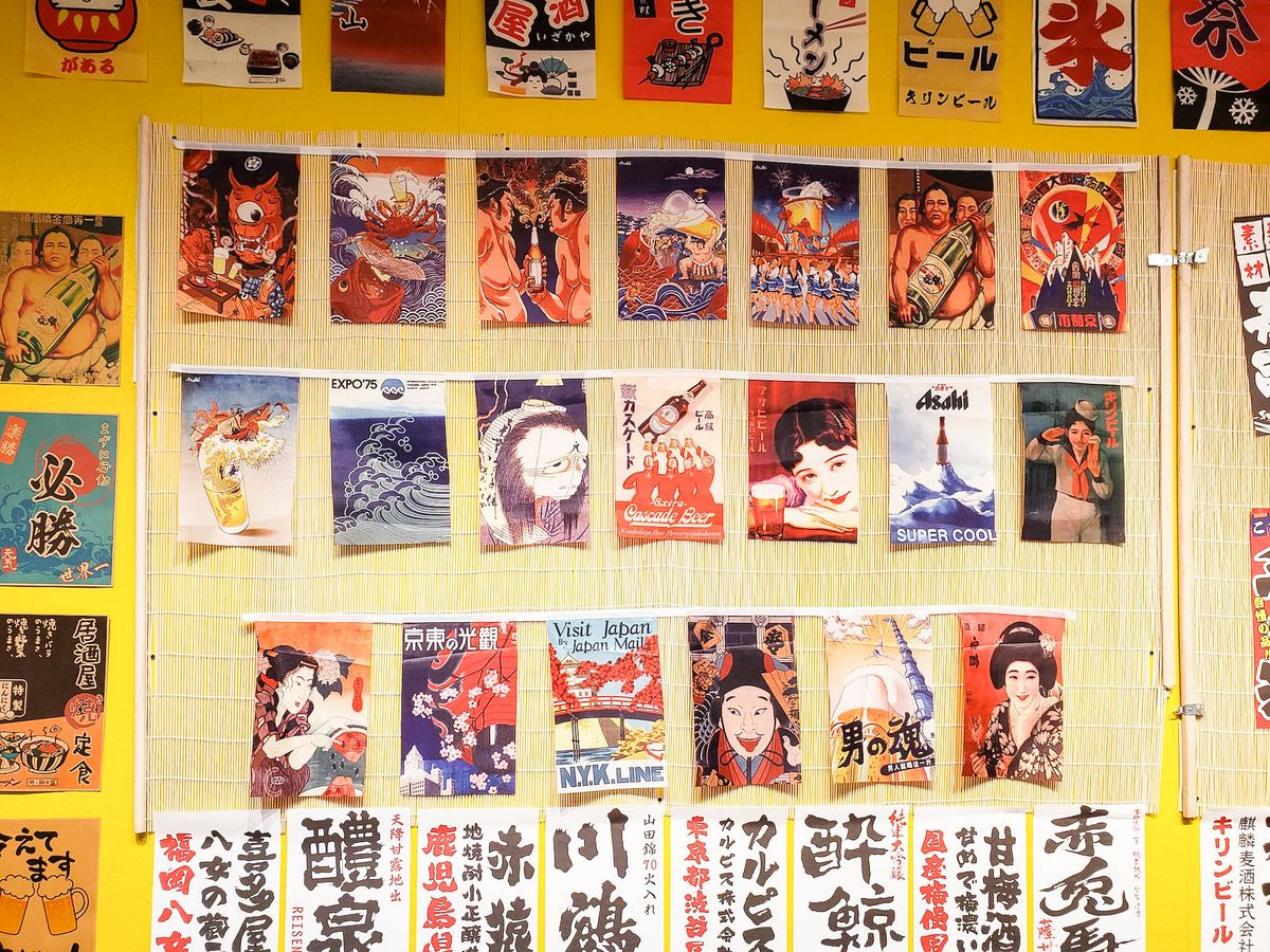 A bamboo-wrapped wall shows off small posters of manga covers.