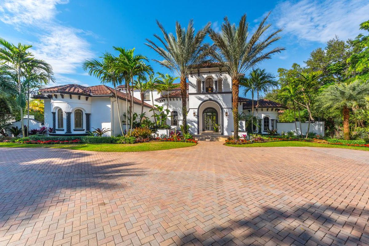 A gorgeous white Mediterranean home in Pinecrest with glorious palms out front and arched entry.