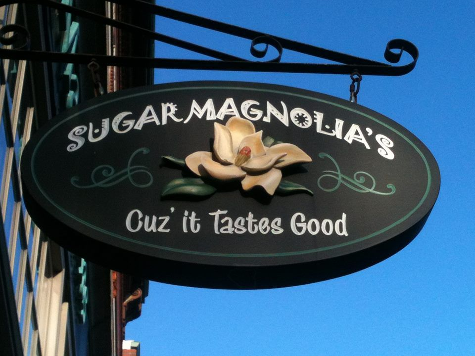 """Closeup on an oval-shaped restaurant sign that says """"Sugar Magnolia's —cuz it tastes good"""" in white font on a dark green background, embellished with a flower."""