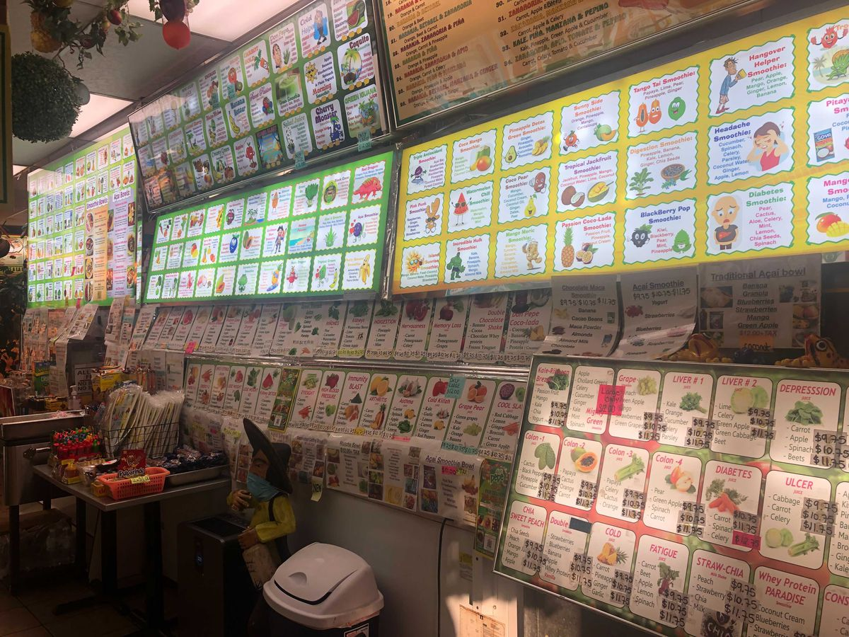A restaurant interior with a bright, colorful menu covering the wall showing dozens of drink varieties and ingredients.
