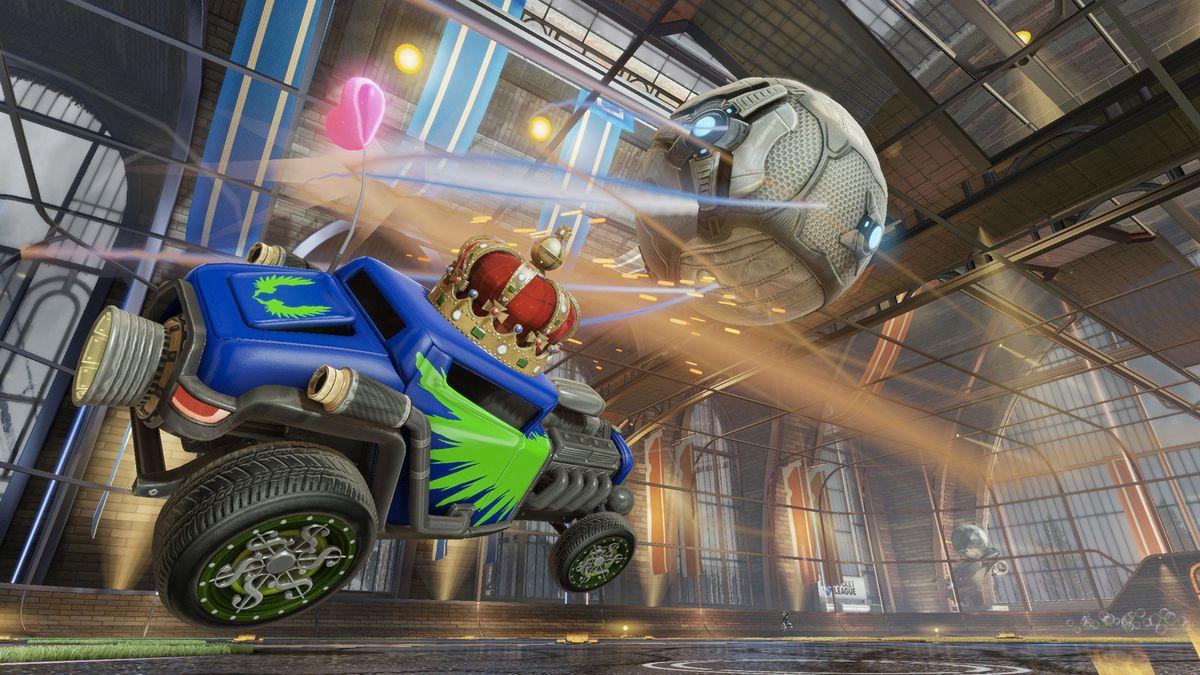 A Rocket League car with a crown on jumps toward the ball