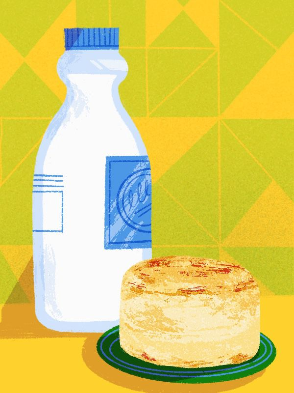 A bottle of buttermilk sits next to a biscuit on a plate.