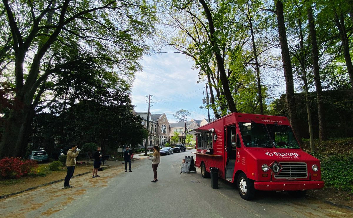 The bright red Refuge Coffee truck parked along a tree-lined street with four people in sweaters and coats talking and sipping coffee in a socially distant circle in the street
