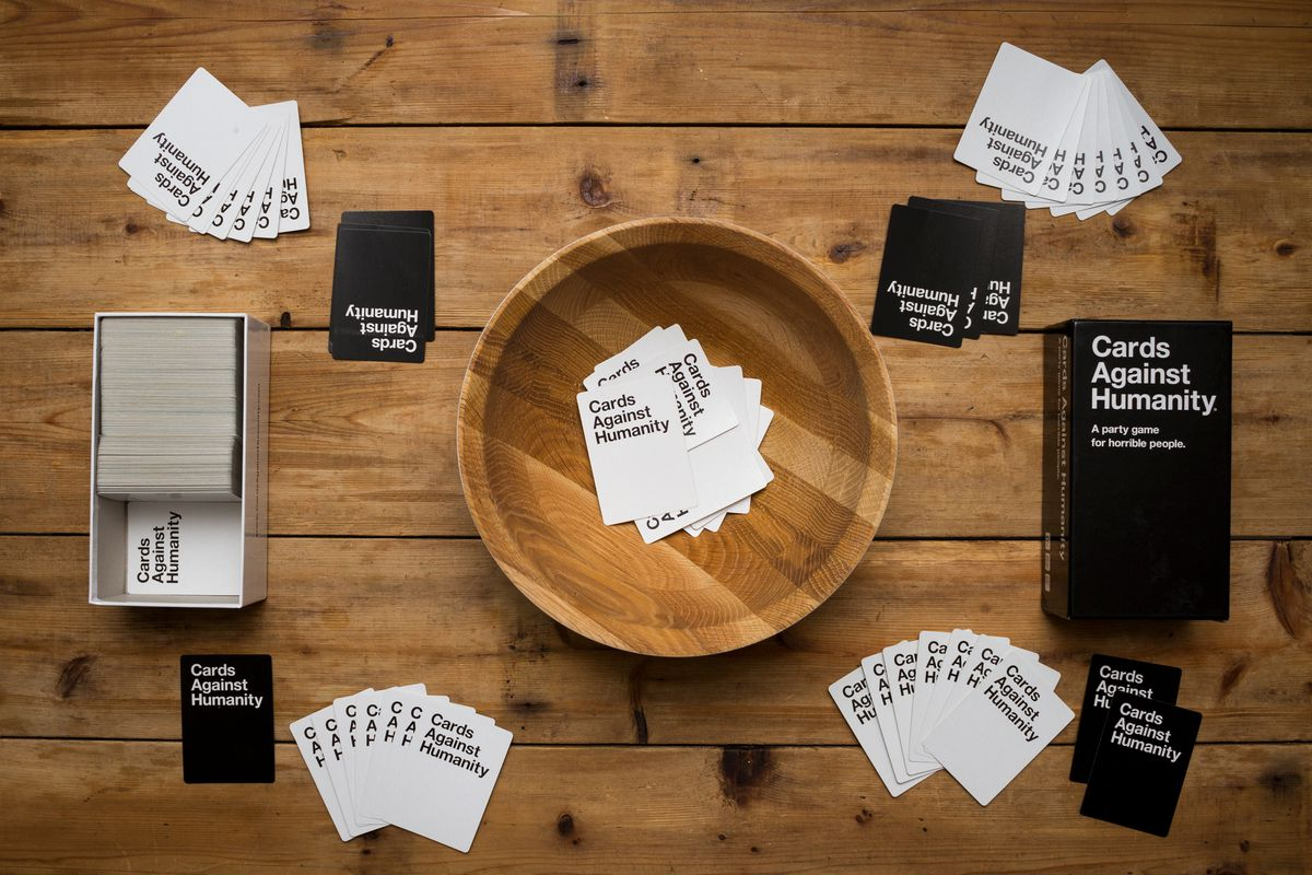 """Piles of black and white cards that read """"Cards Against Humanity"""" sit on a wooden table."""