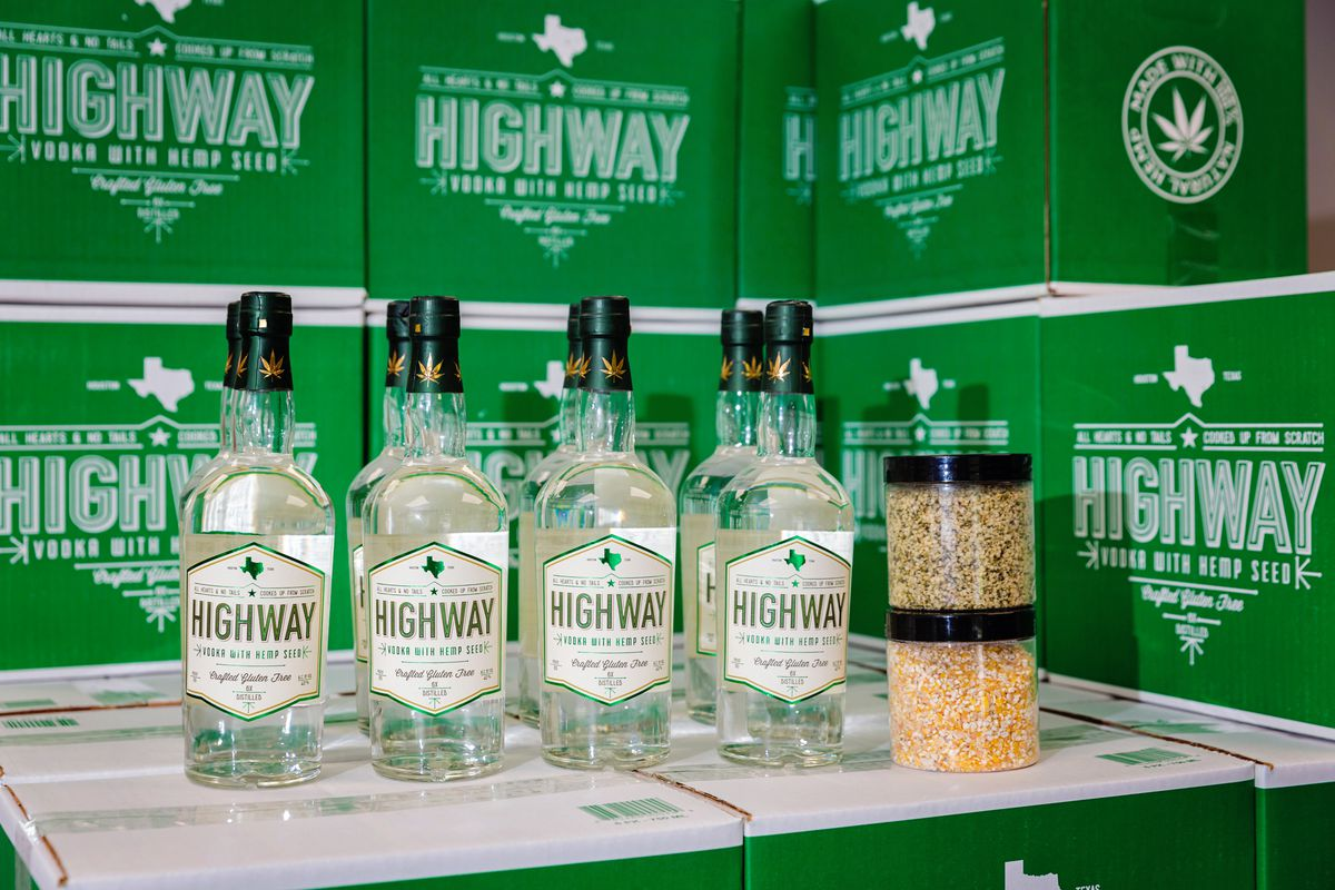 Bottles of Highway Vodka sit on green cardboard boxes. Clear containers of hemp seed and corn sit to the right of the bottles.