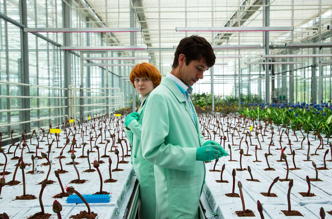 Two scientists standing in a laboratory surrounded by flowers.