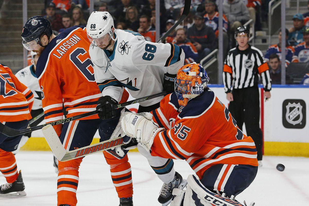 Mar 14, 2018; Edmonton, Alberta, CAN; San Jose Sharks forward Melker Karlsson (68) and Edmonton Oilers defensemen Adam Larssen (6) battle in front of goaltender Al Montoya (35) during the second period at Rogers Place. Mandatory Credit: Perry Nelson