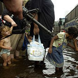 Hurricane Katrina refugees wade through floodwaters to a chartered bus outside the Hyatt Regency Hotel in New Orleans Thursday. A line of people a half-mile long snaked from the Superdome through the nearby Hyatt, then to where evacuation buses waited, early Thursday afternoon.