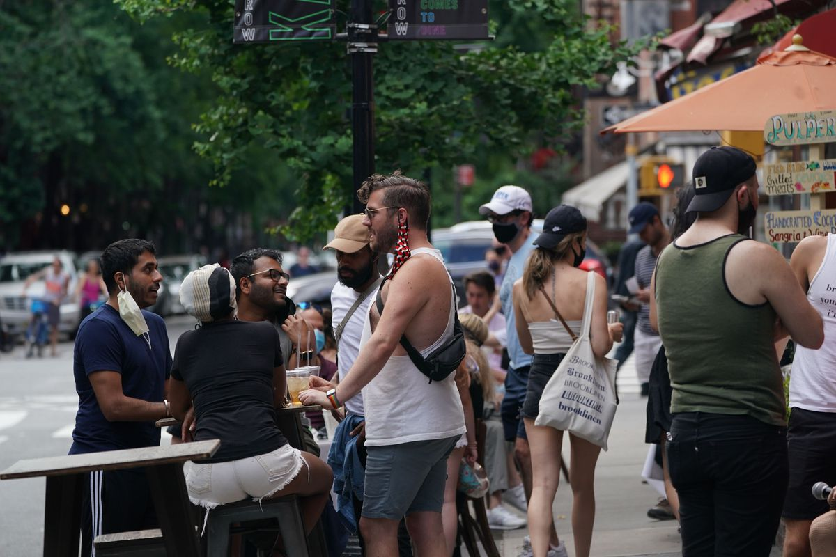People drink outdoor at bars and restaurants in the Hells Kitchen neighborhood of New York on June 7, 2020