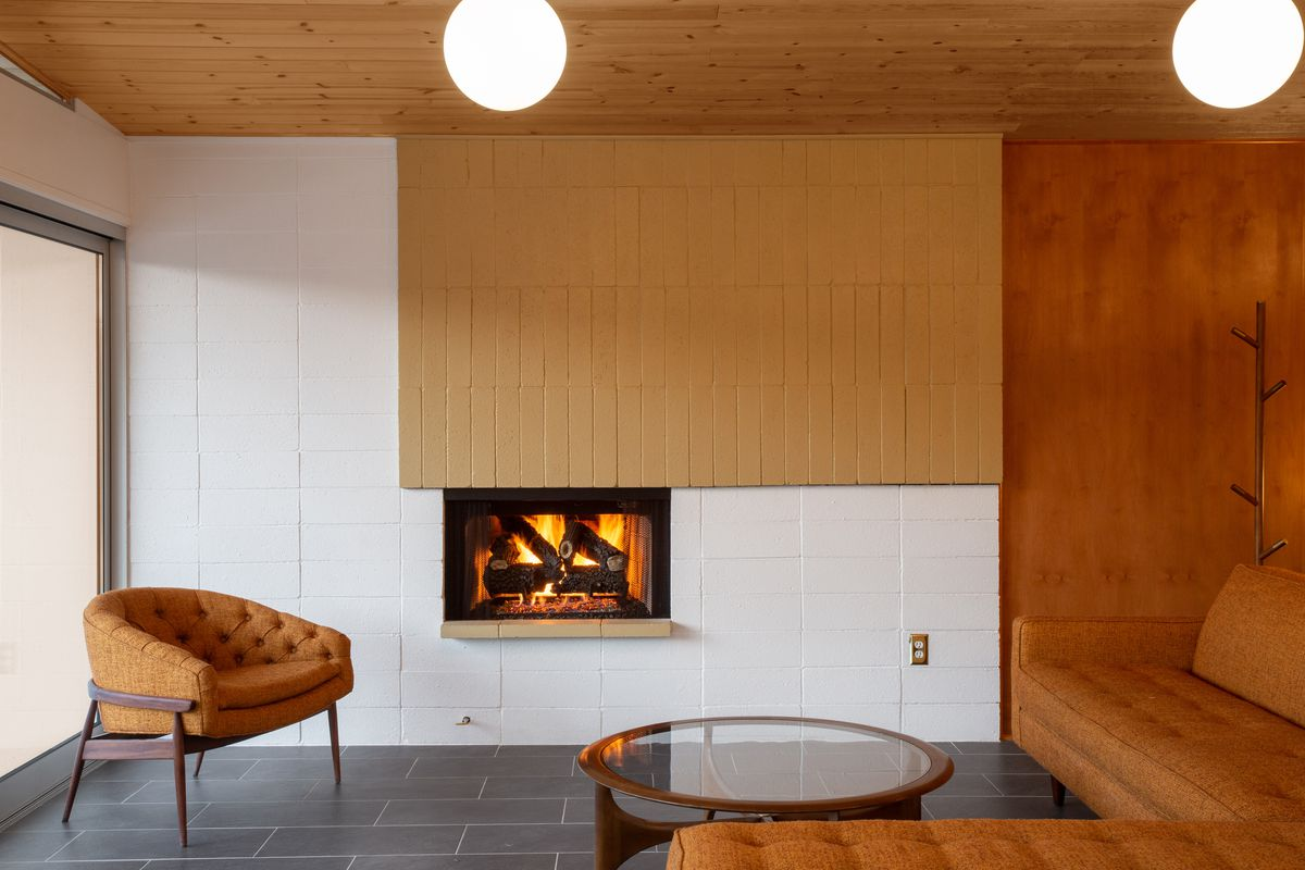 A sitting area around a lit fireplace. There is a brown couch, brown chair, and coffee table around the fire.