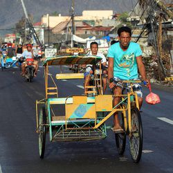 People move through the streets of Tacloban, Friday, Nov. 22, 2013.