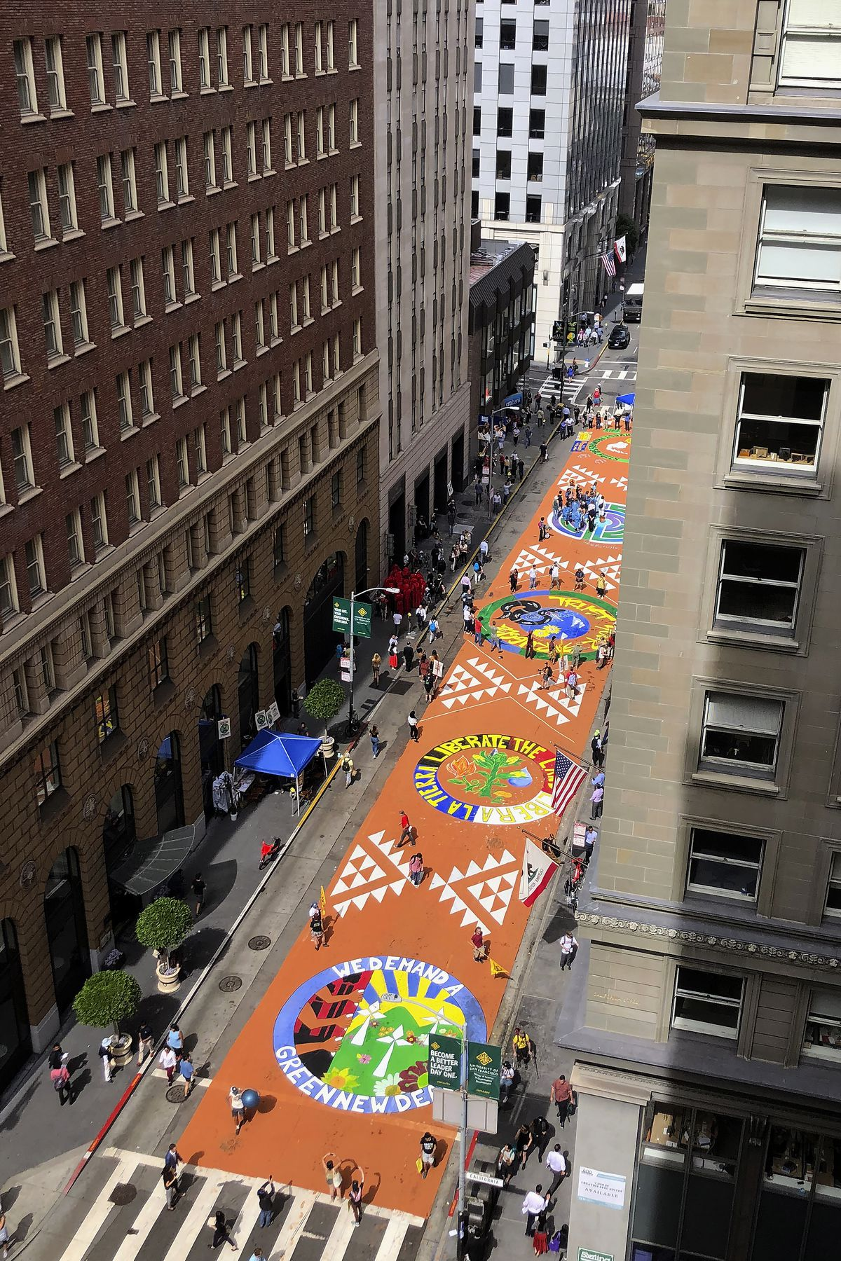 Block-long mural on pavement as seen from an office building on street.