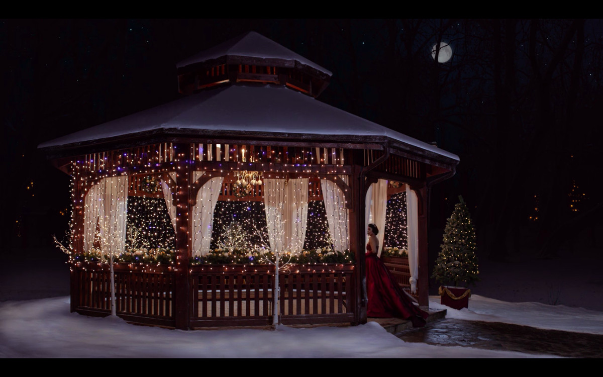A gazebo covered in twinkle lights at nighttime