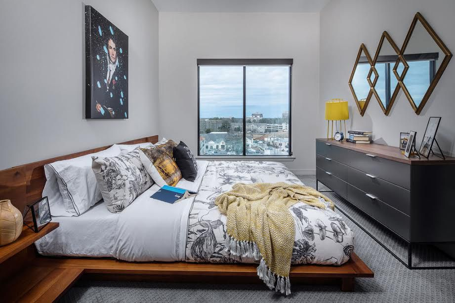 A white bedroom with city views.