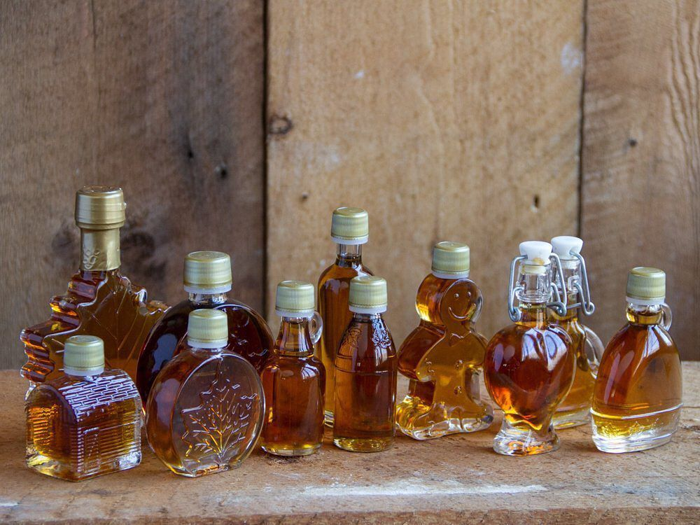 A variety of glass bottles of Vermont's Purinton Maple Syrup, sitting on a wooden table next to a wood wall.