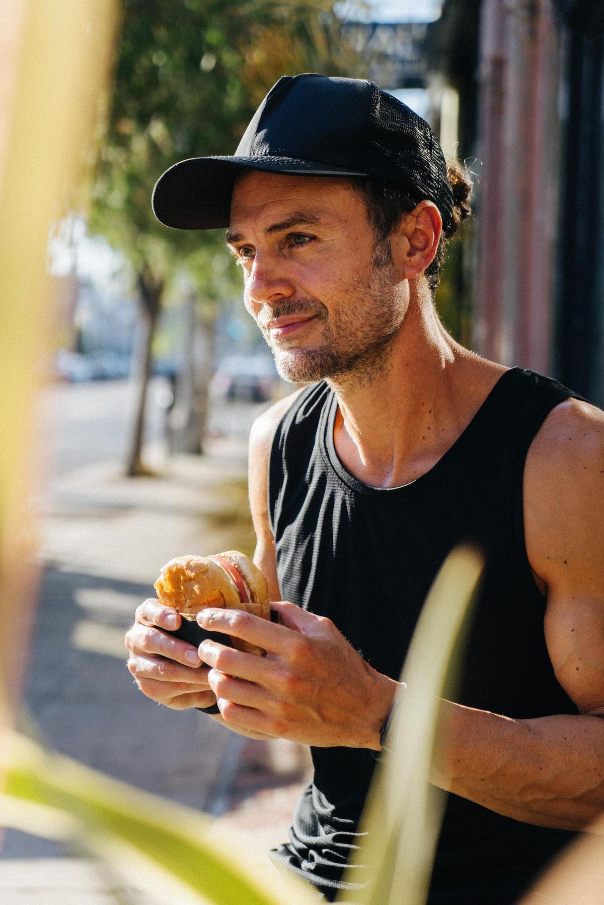 A chef in a black tank top holds a burger as shot through two plants.